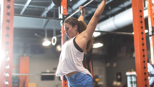 Woman doing pull ups during a cross training workout